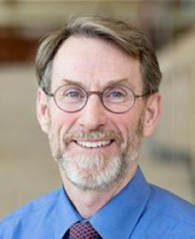 A man with brown hair, a grey beard, wearing glasses and a blue shirt.