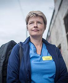 A woman with cropped hair, wearing a blue nurse's scrubs and a navy blue fleece.