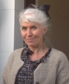 A woman with grey hair tied up, and a taupe cardigan.