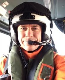 A man in a helmet and helicopter paramedic uniform.