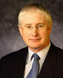 A man with blond hair, glasses and a black suit.