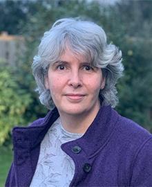 A woman with short grey hair, wearing a purple fleece.