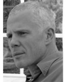 A black and white photo of a man with grey hair and a shirt on.
