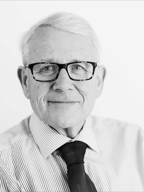A black and white image of a man with grey hair, black glasses, and wearing a shirt and tie.