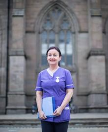 A woman standing in front of a church wearing a purple nurse's scrubs.