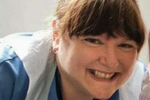 A nurse smiling, wearing a blue uniform and plastic apron.