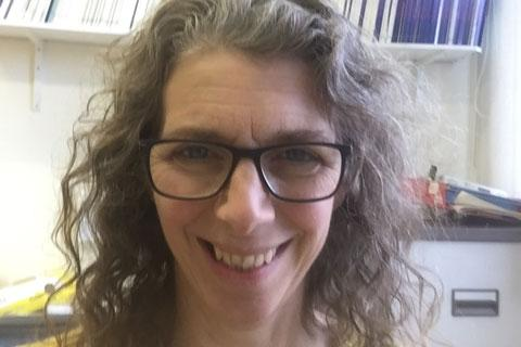 A woman with curly hair and glasses.