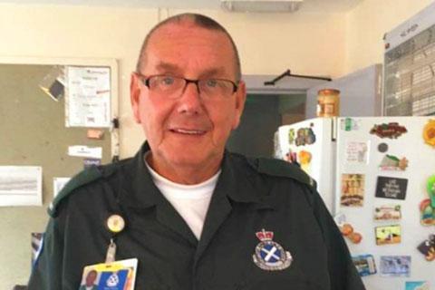 A man in green paramedics uniform.