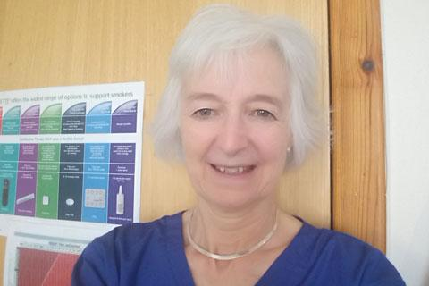 A woman with short grey hair, wearing a blue top.