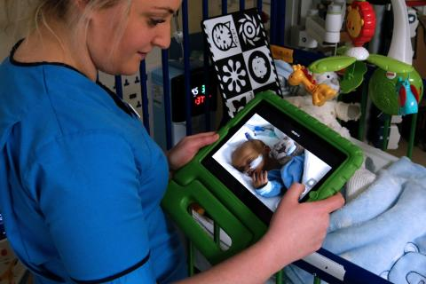 A nurse in a blue uniform, looking at a scan of a baby.